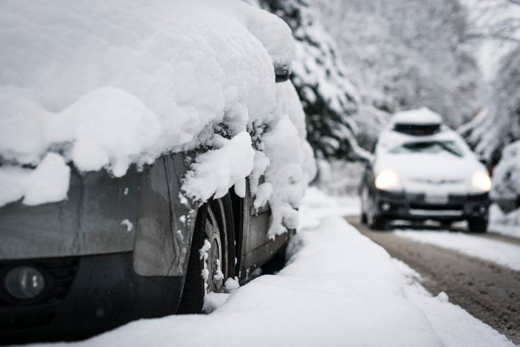 Snow-covered street and car