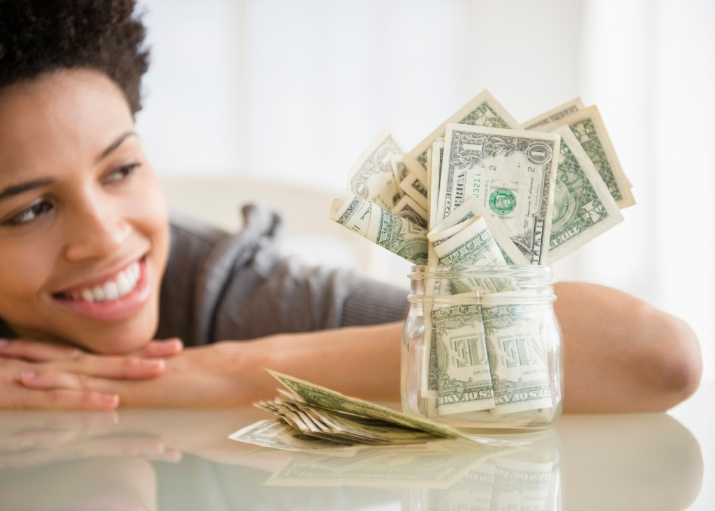 Black woman admiring saved money in jar
