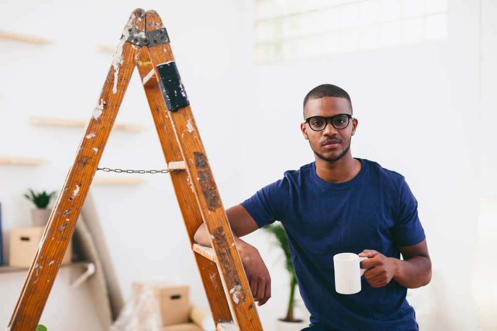 Young man leaning on step ladder having a coffee break