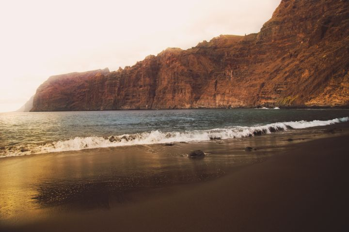 Stunning landscape of the Los Gigantes cliffs with the beach during sunset light with vibrants colors during travel vacations in Tenerife island.