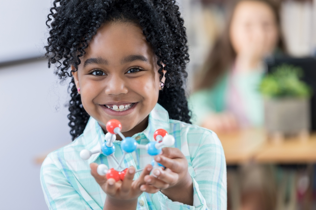 Adorable elementary student showing molecular structure model