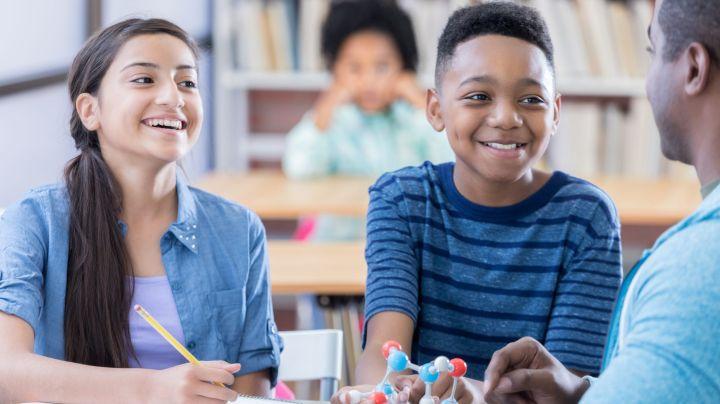 Two preteen students listen to Chemistry teacher define an atom