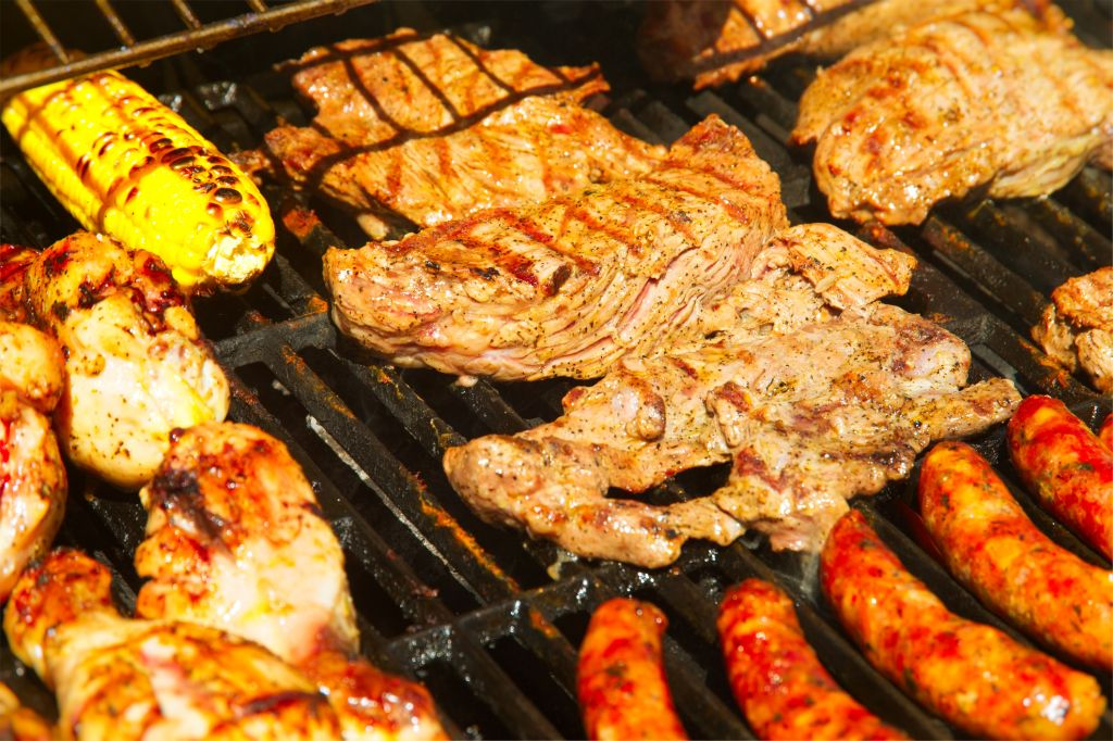 Barbecue grill with chicken, stakes, chorizo, corn and arepas, make a traditional Colombian barbecue